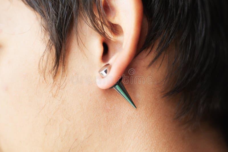 Esticando as orelhas para túneis do diâmetro maior, a mão do perfurador introduz a perfuração na orelha imagem de stock royalty free