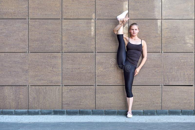 Esticando a mulher da ginasta que faz a separação do vertical, guita no fundo urbano marrom da parede fotos de stock royalty free