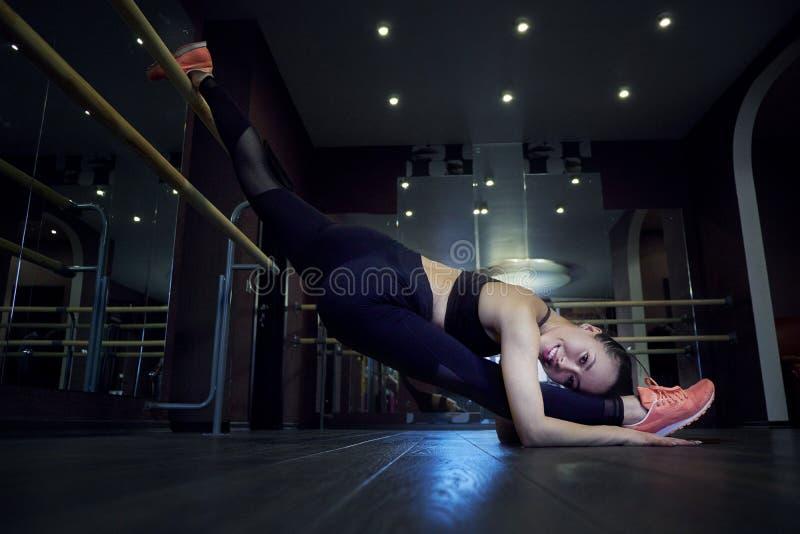 Esticando a mulher da ginasta que faz a separação vertical, guita Opinião lateral a jovem mulher atrativa que faz o exercício imagem de stock royalty free