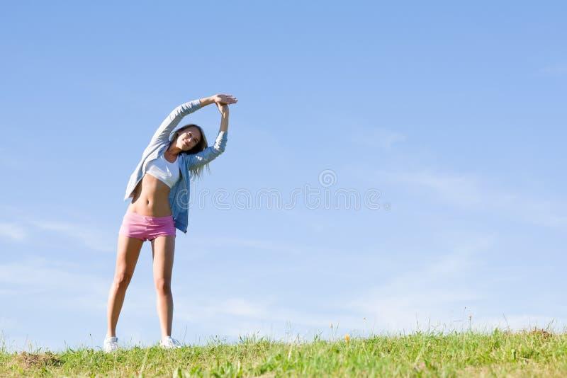Esticando o dia ensolarado dos prados sportive novos da mulher fotografia de stock royalty free