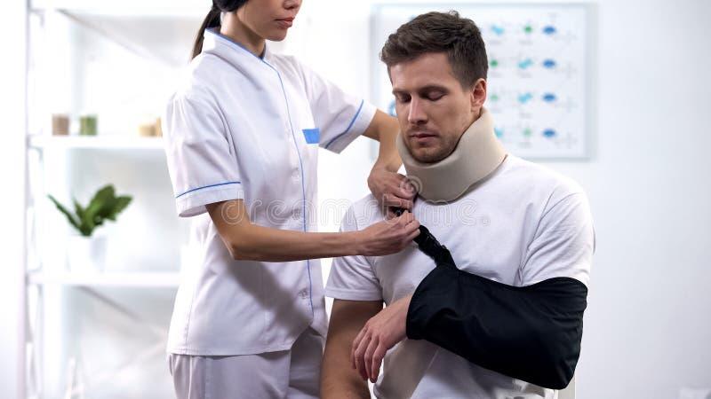Estilingue paciente masculino do braço da fixação do ortopedista na posição direita, reabilitação após o traumatismo fotografia de stock royalty free