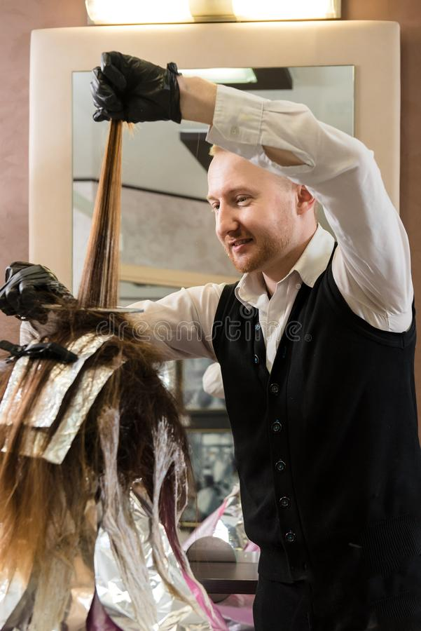 Estilista com tintura de cabelo e cabelo colorindo da escova no salão de beleza foto de stock royalty free