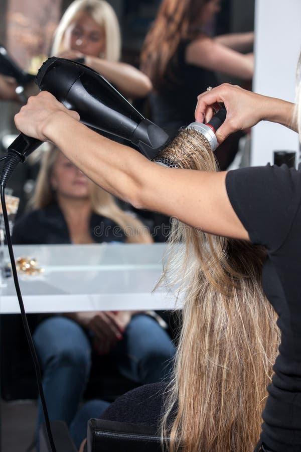 Estilista con el trabajo del ventilador sobre el pelo de la mujer en salón foto de archivo