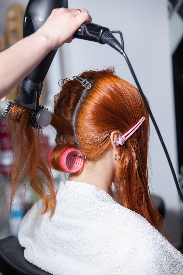 Estilista de cabelo com trabalho do ventilador no cabelo da mulher fotografia de stock