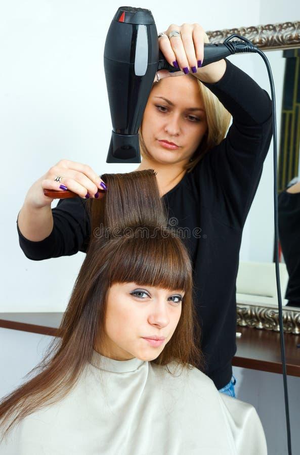 Estilista de pelo con el ventilador del pelo fotos de archivo