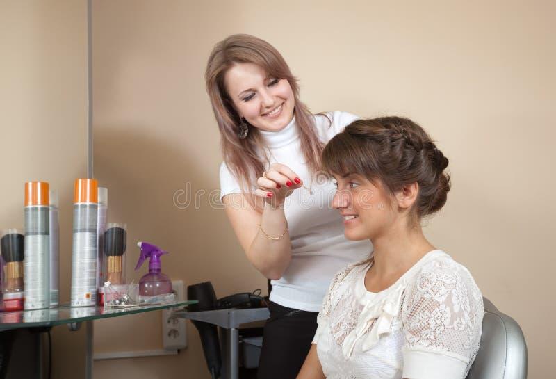 Estilista de pelo que trabaja con la muchacha de pelo largo fotos de archivo