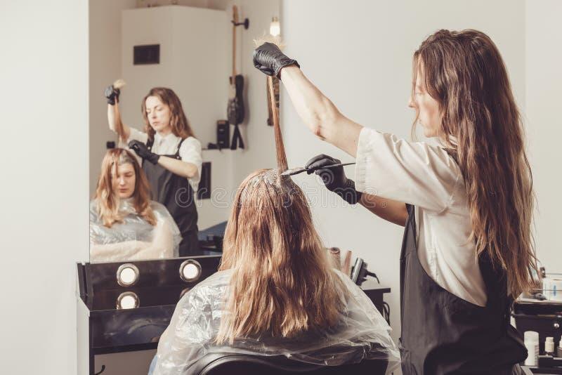 Estilista de sexo femenino que aplica un tinte al pelo de los clientes foto de archivo