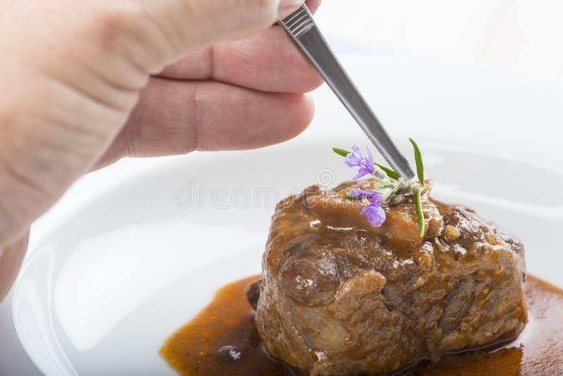Estilista do alimento que trabalha em uma placa do guisado do rabo de boi imagem de stock royalty free