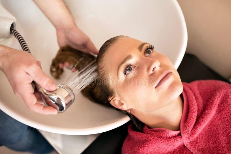 Estilista en el trabajo, pelo que se lava del peluquero al cliente imagen de archivo libre de regalías
