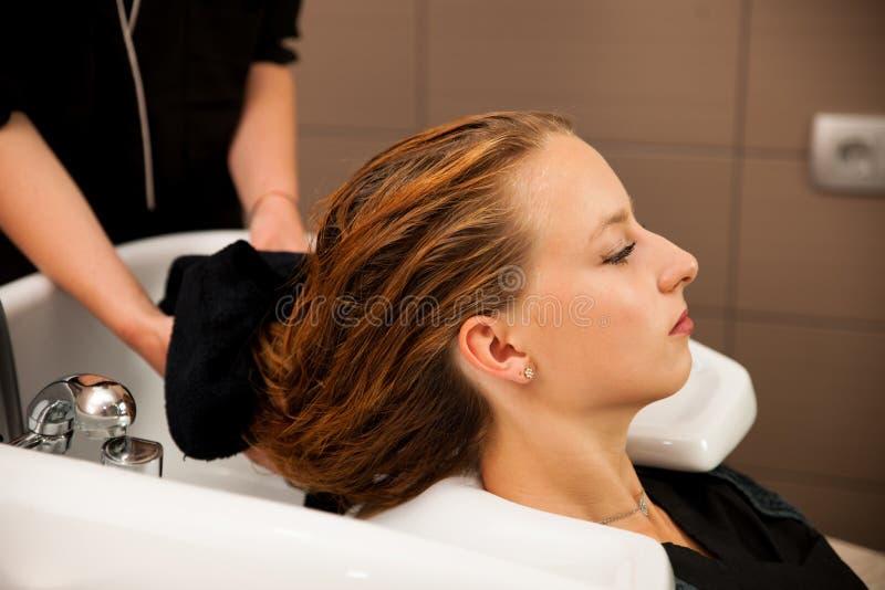 Estilista en el trabajo - pelo que se lava del peluquero al cliente imagenes de archivo