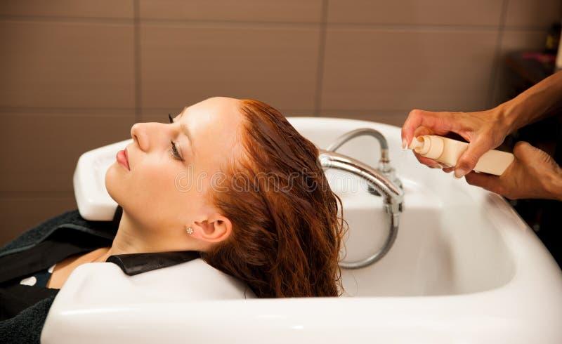 Estilista en el trabajo - pelo que se lava del peluquero al cliente imágenes de archivo libres de regalías
