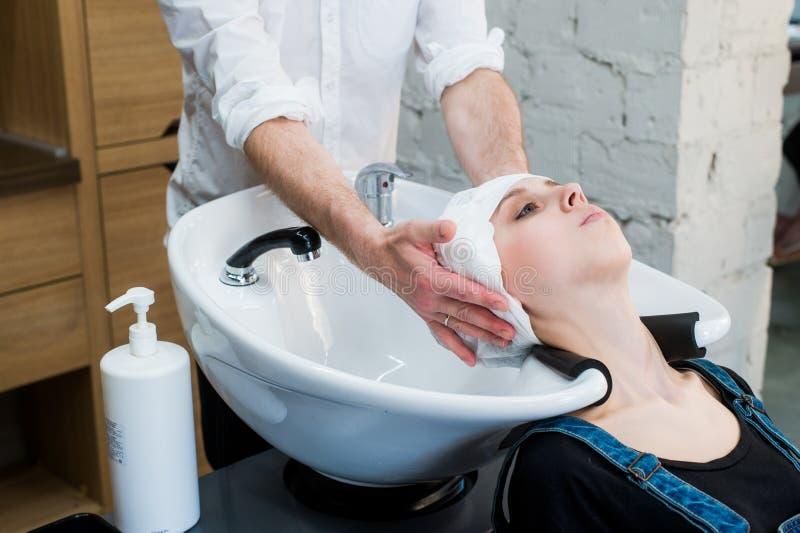 Estilista en el trabajo - pelo que se lava del peluquero al cliente antes de hacer el peinado fotos de archivo libres de regalías