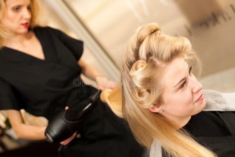 Estilista profesional en el trabajo - peluquero que hace el peinado imágenes de archivo libres de regalías