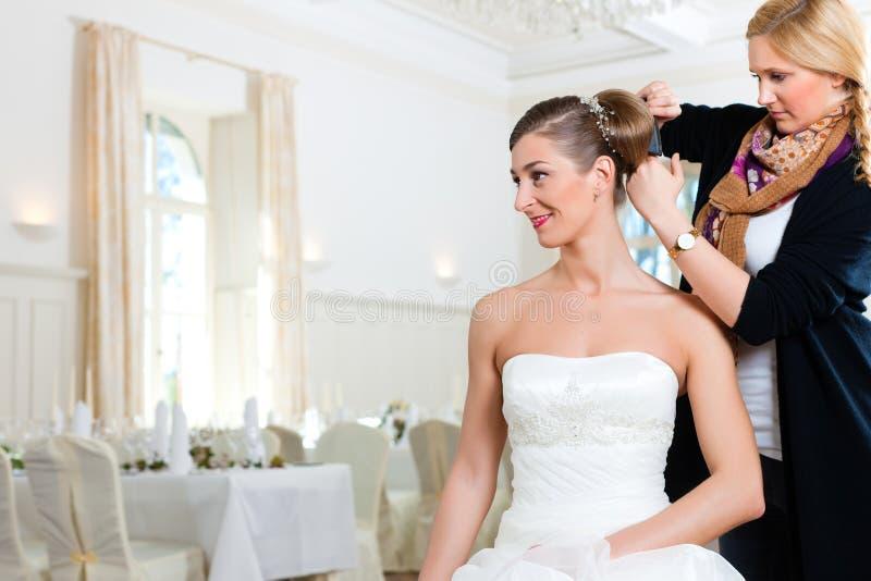 Estilista que fixa acima do penteado de uma noiva imagens de stock royalty free