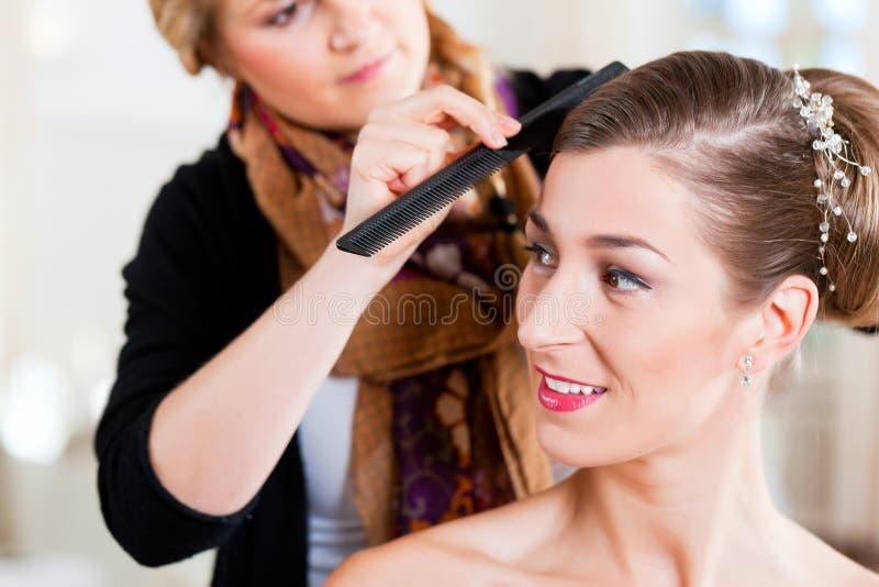 Estilista que fixa acima do penteado de uma noiva foto de stock royalty free