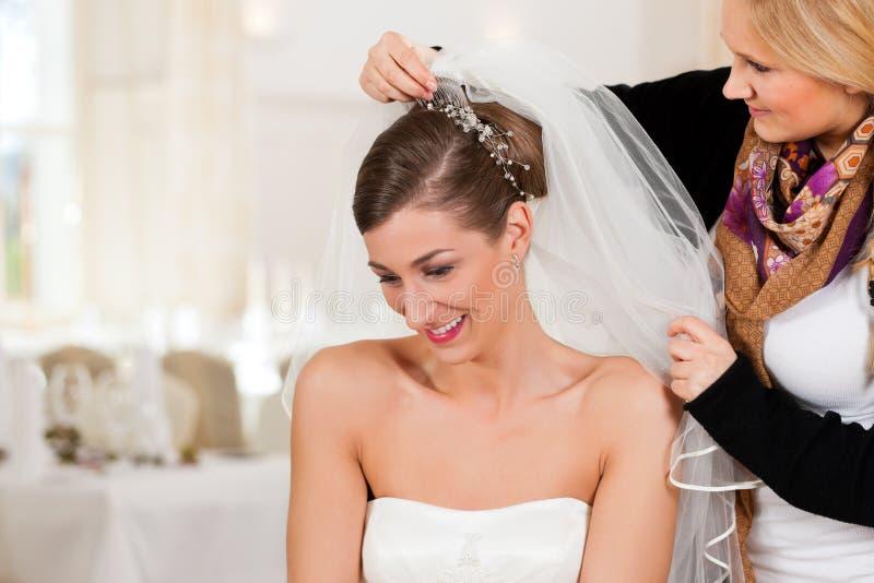Estilista que fixa acima do penteado de uma noiva foto de stock