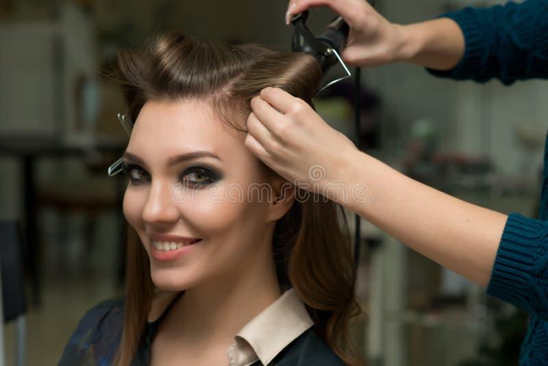 Estilista que hace rizos a la mujer morena Trabajo del peluquero imagen de archivo