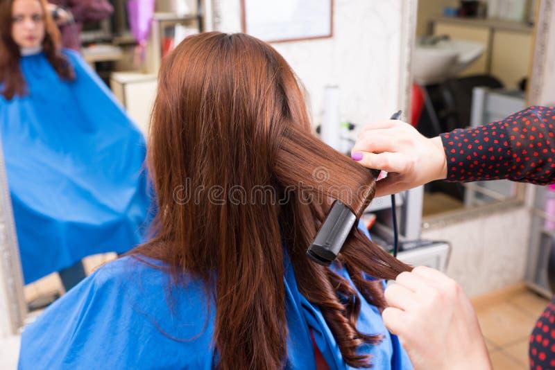 Estilista que usa el hierro plano en el pelo del cliente moreno foto de archivo libre de regalías