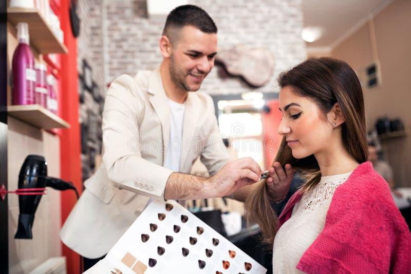 Estilista y cliente en el salón de los cosméticos, haciendo un nuevo pelo s imágenes de archivo libres de regalías