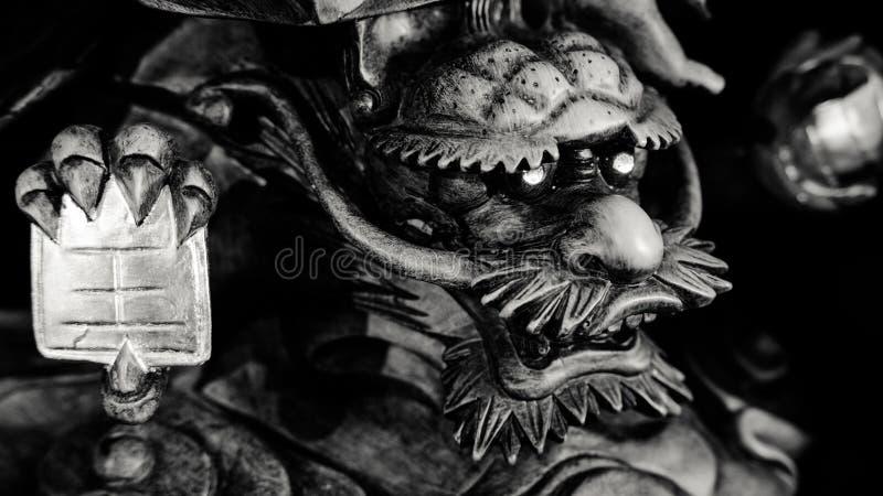 Estilo blanco y negro del chino Dragon Statue bajo pie de la estatua de Guanyin Buda con el fondo oscuro ligero foto de archivo libre de regalías