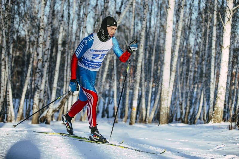 Estilo clássico do esquiador masculino novo em uma floresta do vidoeiro do inverno em fugas imagem de stock royalty free