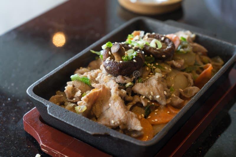 Estilo coreano de la comida; cerdo y proliferar r?pidamente comida frita en la cacerola cuadrada en la placa de madera foto de archivo libre de regalías