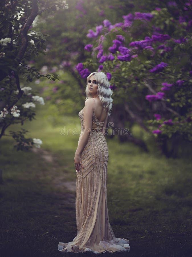 Estilo da mola Louro sensual bonito da menina na mola Jardim de florescência da mola Moça em um vestido elegante do ouro fotos de stock royalty free