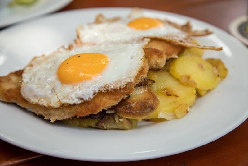 Estilo de Hamburgo del escalope de la carne de cerdo con los huevos fritos y las patatas de la carne asada en el restaurante de B fotografía de archivo libre de regalías