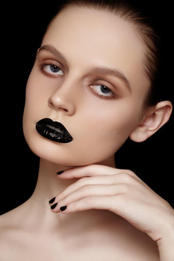 Estilo de la alta moda, manicura. Modelo hermoso con los labios y los clavos negros imagen de archivo libre de regalías