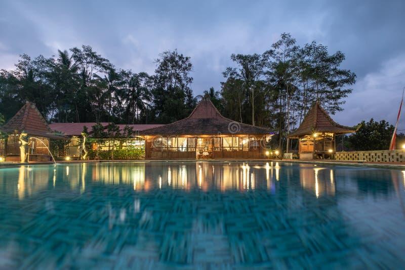 Estilo de madera de Banyuwangi, de Indonesia - Bali del centro turístico de la arquitectura con la piscina e iluminación en oscur imágenes de archivo libres de regalías