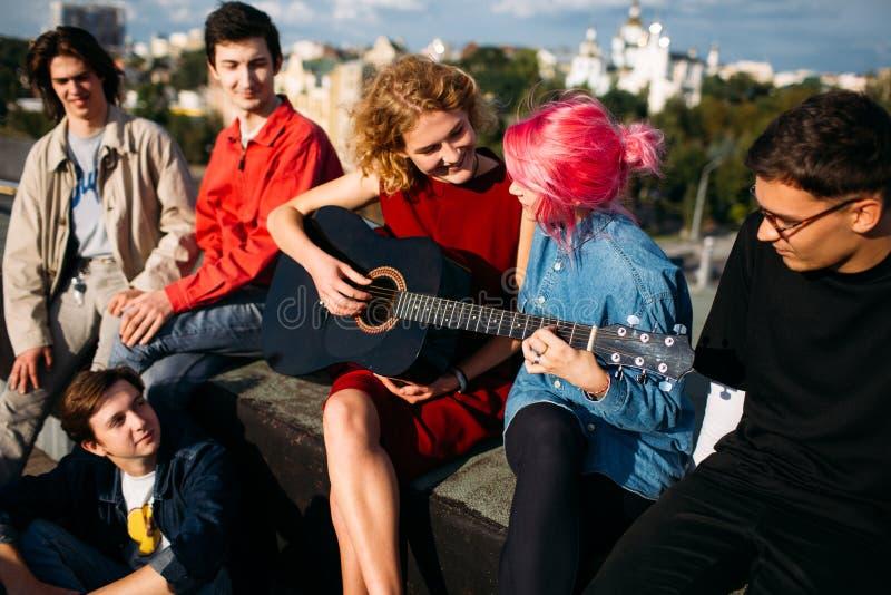 Estilo de vida adolescente do moderno dos amigos do jogo das lições da guitarra foto de stock