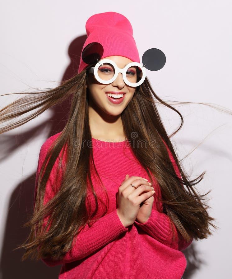 Estilo de vida, beleza e conceito dos povos: Menina de sorriso bonito nova que veste a camiseta cor-de-rosa e óculos de sol engra imagens de stock