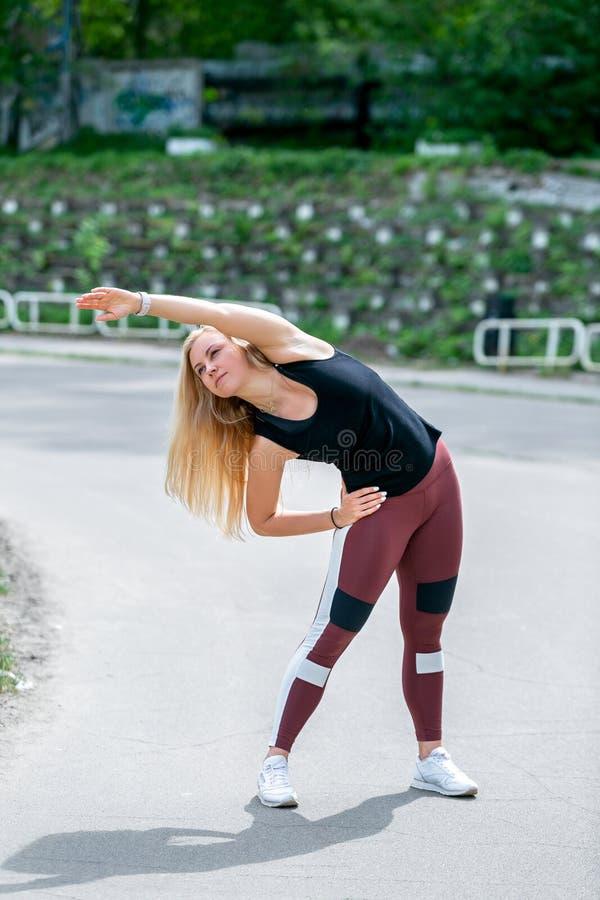 Estilo de vida da aptid?o A jovem mulher que aquece-se antes de fazer de forma??o exercita para esticar seus m?sculos e jun??es E foto de stock