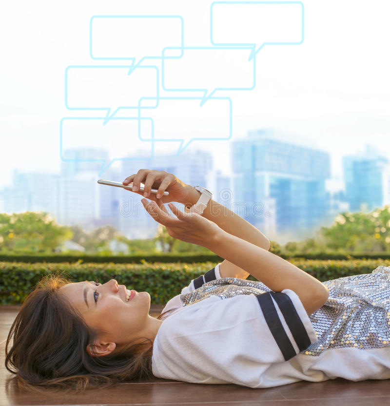 Estilo de vida de ciudad de la mujer asiática que miente y que toca en phon móvil foto de archivo libre de regalías