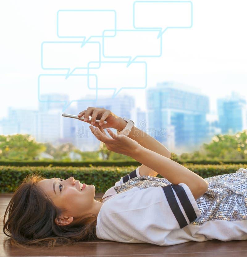 Estilo de vida de ciudad de la mujer asiática que miente y que toca en phon móvil imagenes de archivo