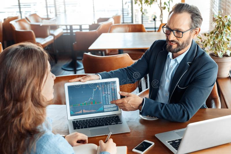 Estilo de vida do negócio Comerciante nos monóculos que sentam-se no café que mostra a carta de troca no portátil ao sorriso da m fotografia de stock