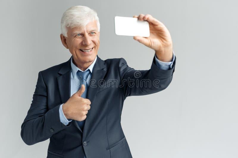Estilo de vida do negócio Posição do homem de negócios isolada no selfie de tomada cinzento no polegar da exibição do smartphone  fotos de stock