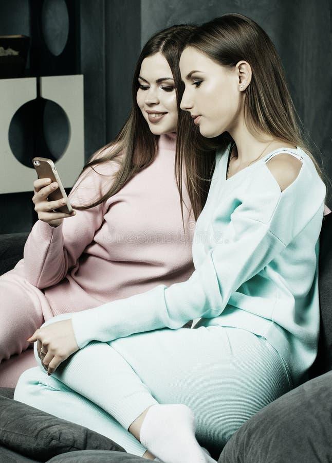 Estilo de vida e conceito dos povos: Duas mulheres bonitas que olham o telefone celular em casa imagens de stock royalty free