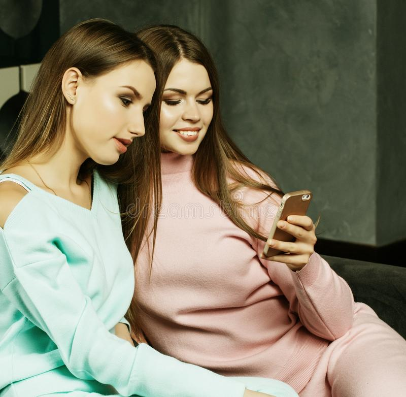 Estilo de vida e conceito dos povos: Duas mulheres bonitas que olham o telefone celular em casa foto de stock royalty free
