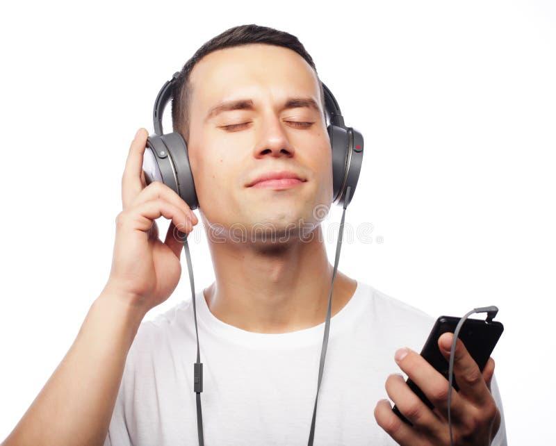 Estilo de vida e conceito dos povos: Homem novo que aprecia a música no seu ele imagem de stock
