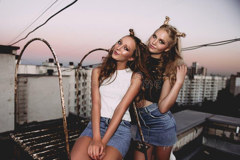 Estilo de vida e conceito dos povos: Retrato da forma de dois melhores amigos à moda das meninas que vestem saias das calças de b fotografia de stock royalty free