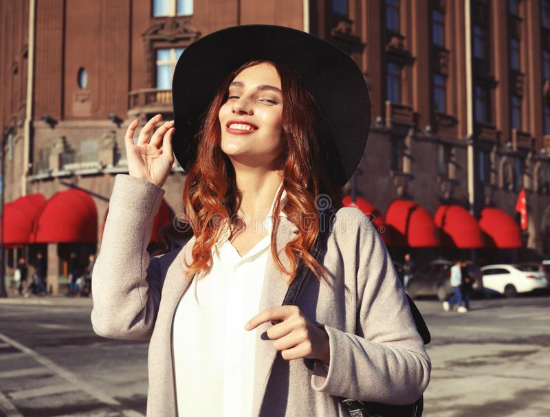 Estilo de vida e conceito dos povos: Retrato exterior da mulher de sorriso feliz bonita de Yong que veste o chapéu à moda, revest foto de stock