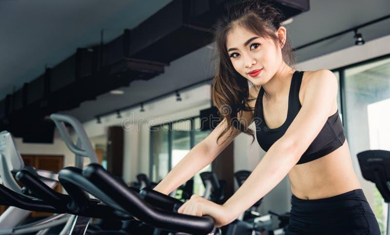 Estilo de vida fêmea da mulher usando a bicicleta de exercício da máquina do equipamento para fotos de stock royalty free