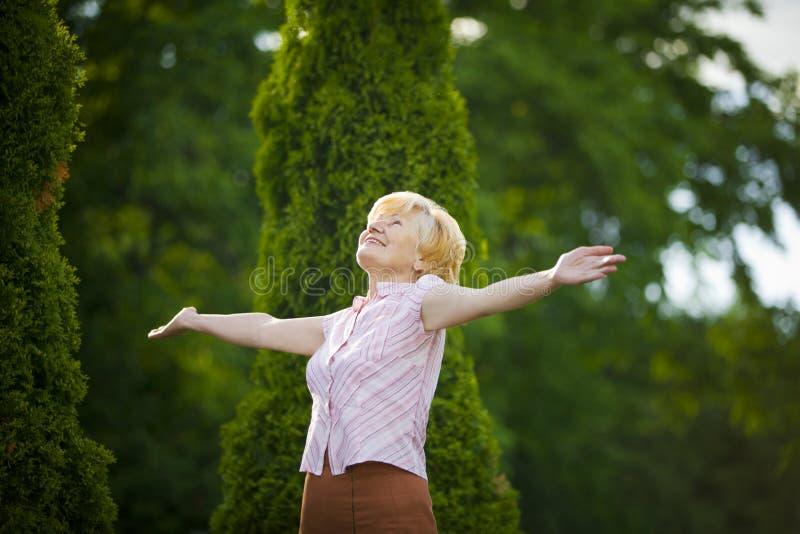 Estilo de vida. Liberdade. Mulher adulta aposentada entusiasmado com braços estendido fotos de stock