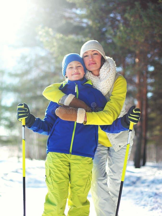 Estilo de vida saudável do inverno da família! A criança da mãe e do filho vai esquiar na floresta fotografia de stock
