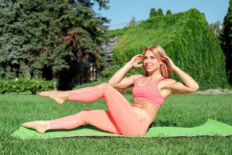 Estilo de vida saudável Ioga praticando da mulher na esteira que faz fora o sorriso do exercício da bicicleta feliz fotos de stock