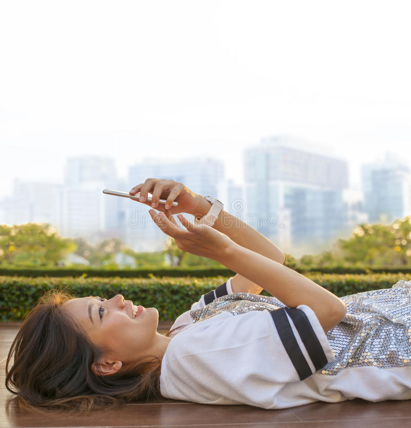 Estilo de vida urbana da mulher asiática que encontra-se e que toca no phon móvel foto de stock