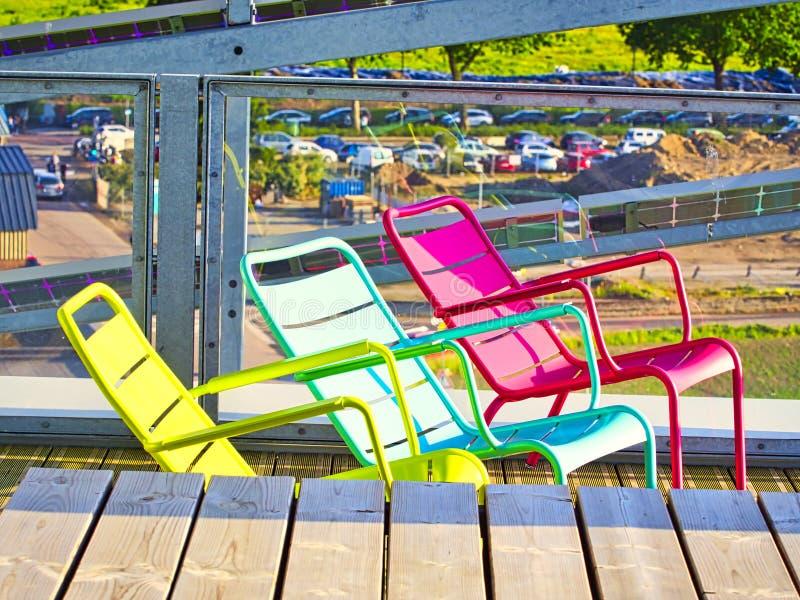 Estilo decorativo moderno el metal tres coloreó sillas en terraza de madera, estilo exterior con muebles y el objeto colorido imágenes de archivo libres de regalías