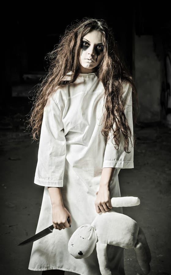 Estilo del horror tirado: muchacha triste extraña con la muñeca y el cuchillo del moppet en manos foto de archivo libre de regalías