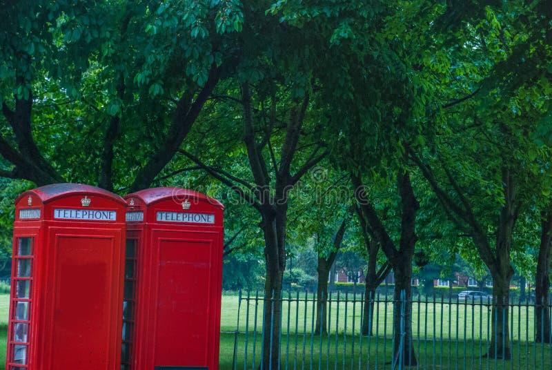 Estilo del vintage de las cabinas de teléfono rojas típicas en la calle lluviosa en Londres imagenes de archivo
